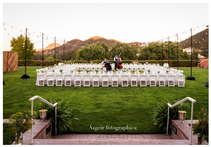 Green lawn with tables and chairs set up for large corporate event, musicians set up to play