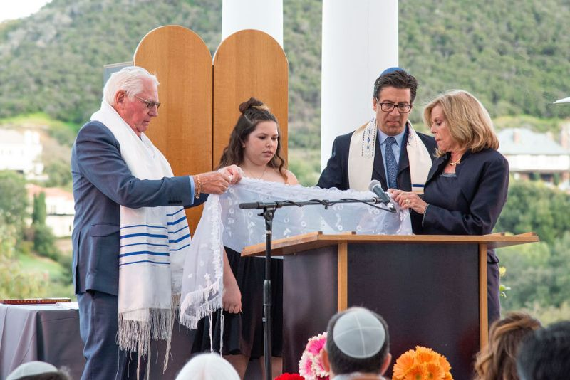 Bat-Mitzvah with cool, classy theme - formal outdoor seating lined up, with young female on stage, preparing for ceremony