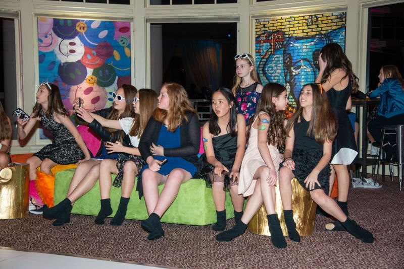 Bat-mitzvah, colorful theme - brightly colored seating area with couches and murals, several young women mingling