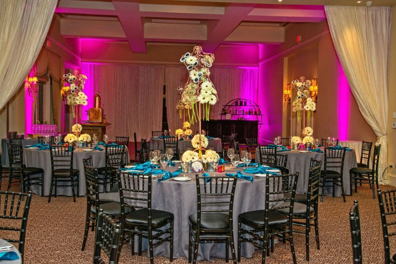 Bat-Mitzvah with cool, classy theme - cream-colored daisy centerpieces, gray tablecloths with bright pink lighting on walls, bark in background