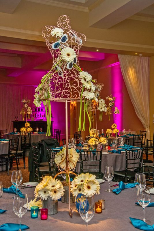 Bat-Mitzvah with cool, classy theme - cream-colored daisy centerpieces, gray tablecloths with bright pink lighting on walls
