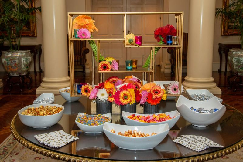 Bat-mitzvah, colorful theme - table with snacks and bright, colorful flower centerpiece