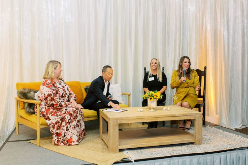People speaking at a corporate event, on stage set with seating and coffee table