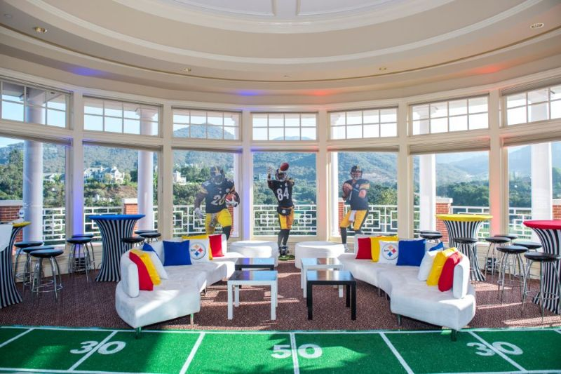 Bar Mitzvah, football theme, seating with colorful pillows and green turf rug