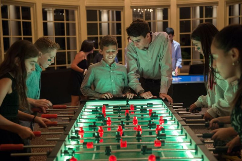 Mitzvah with kids gathered around foosball and air hockey tables