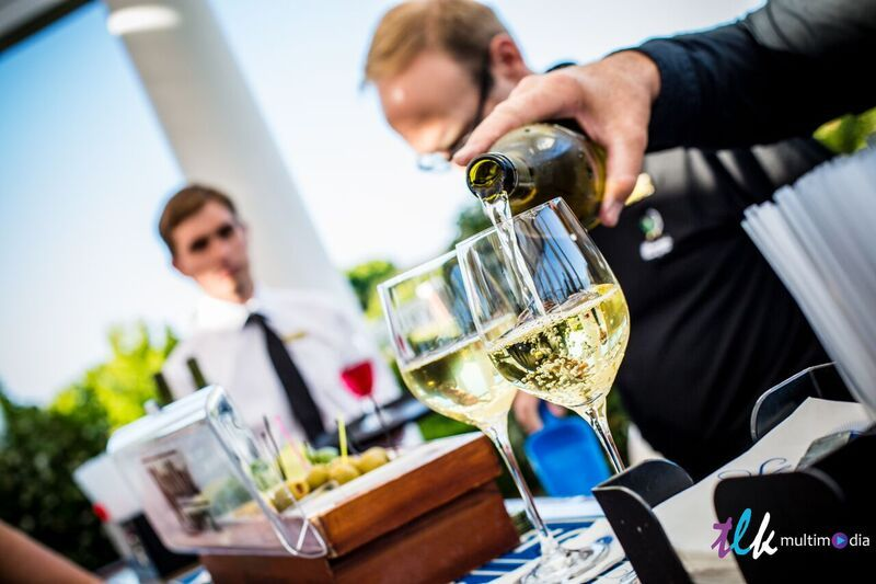 Two glasses of wine being poured at bar set up for corporate event