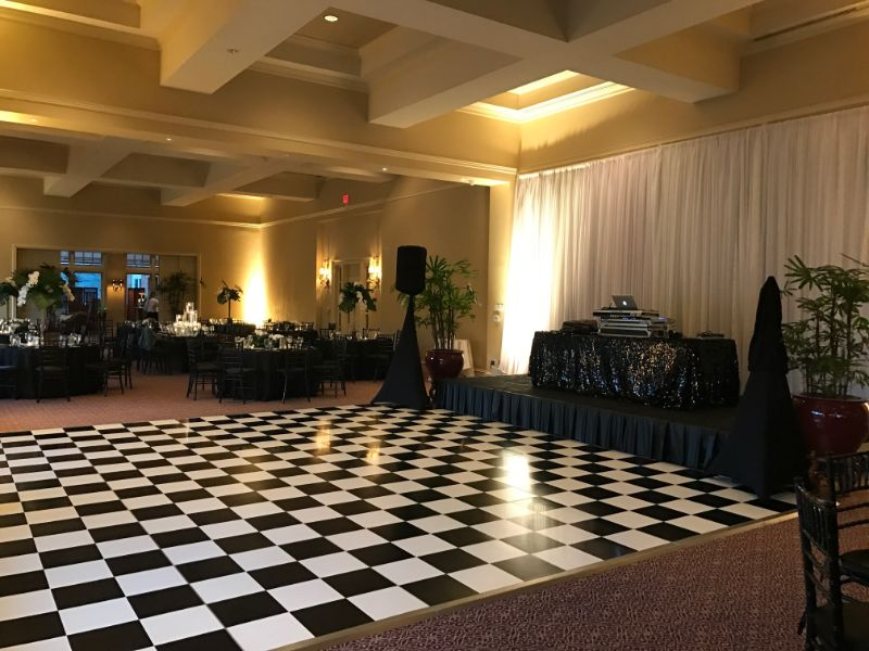 Indoor venue decorated in black and white dance floor, with tables set for guests