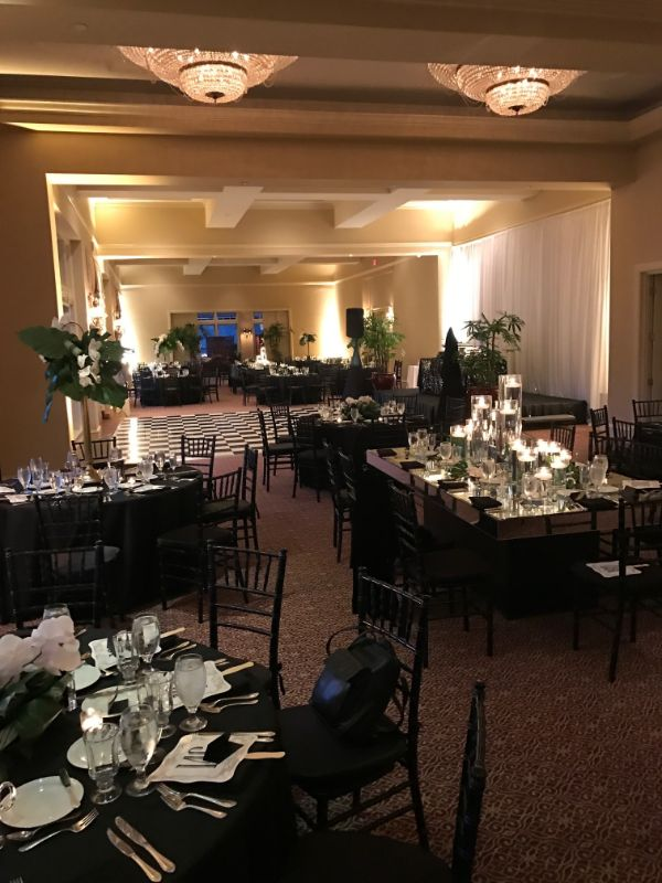 Indoor venue decorated in black and white theme, with tables set for guests