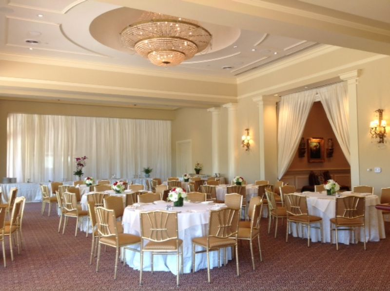 Indoor venue with tables set for guests, white and gold theme