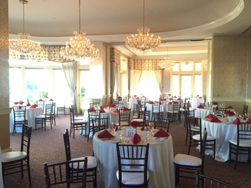 Indoor venue with tables set for guests, white table cloths with red napkins