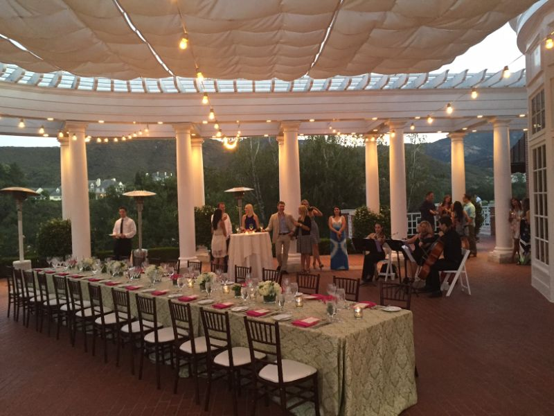 Evening event set up on outdoor patio, long table, musicians playing