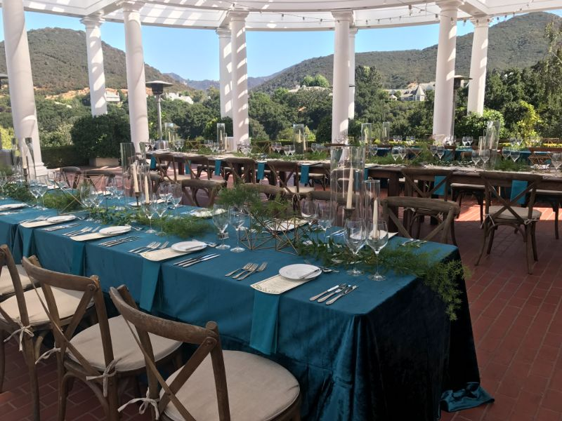 Outdoor patio with long tables set for guests for special event