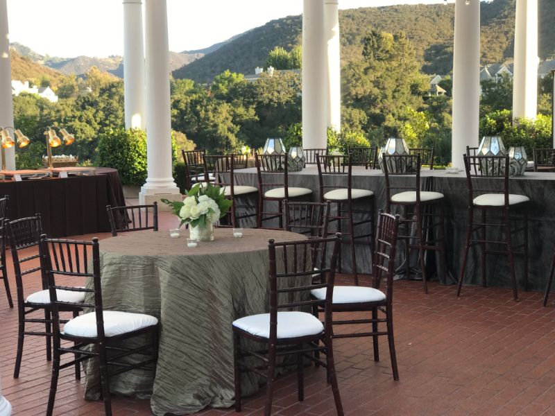 Outdoor patio set with elegantly decorated tables and chairs
