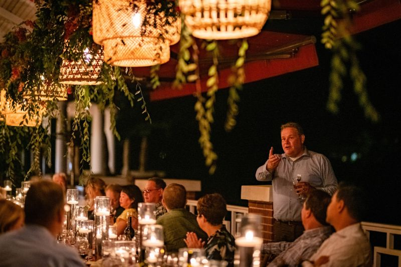 Outdoor evening event with guests, man giving speech