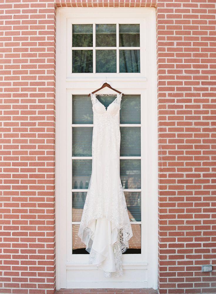 Real Wedding-S&W-Wedding dress on hanger hanging outside window of brick building