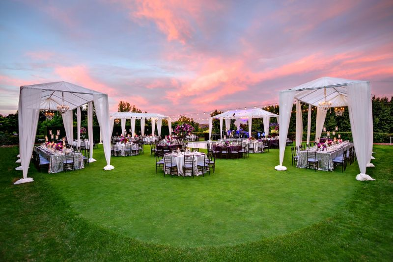 Outdoor evening wedding reception on lawn with long tables set for dinner, with tents, lights, and seating