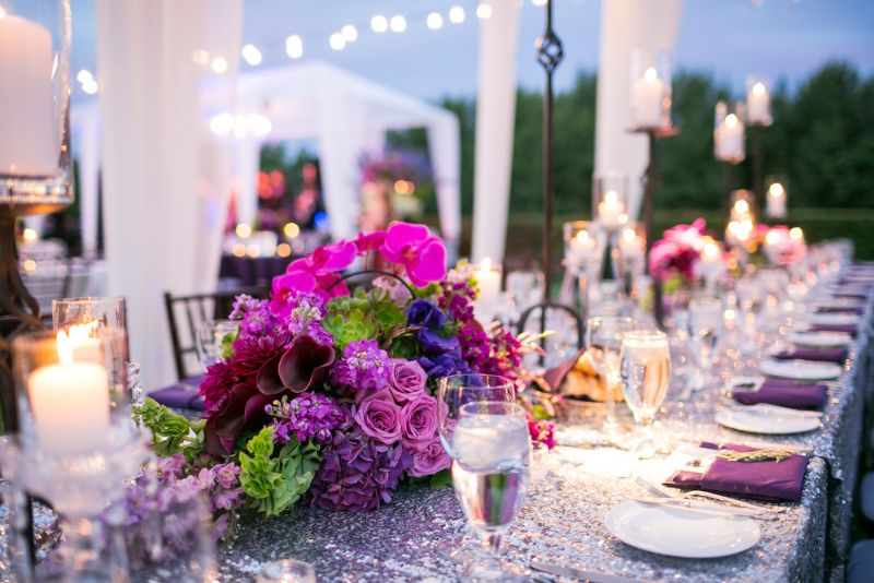 Outdoor evening wedding reception guests on lawn with long tables set for dinner, with tents, lights, and seating