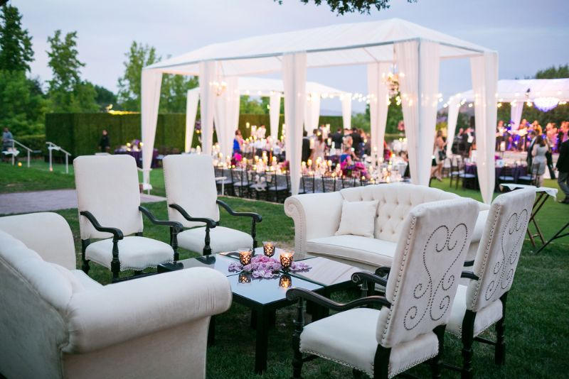 Outdoor wedding reception guests on lawn tables, tents, lights, and seatingwith