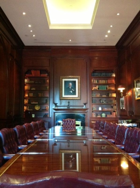 Study-themed banquet room, long, shiny conference table surrounded with leather chairs