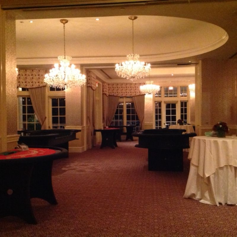 Room set up for casino night event, with several tables for casino games
