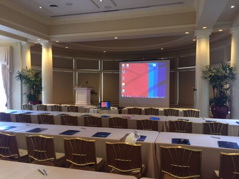 Stage set with podium and screen for presentation, long tables to seat attendees
