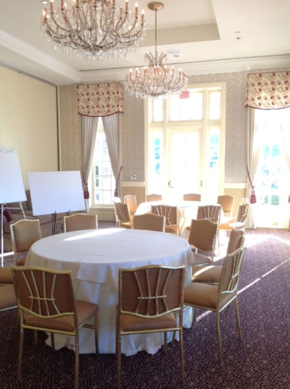 Tables and chairs with whiteboards set up for corporate meeting