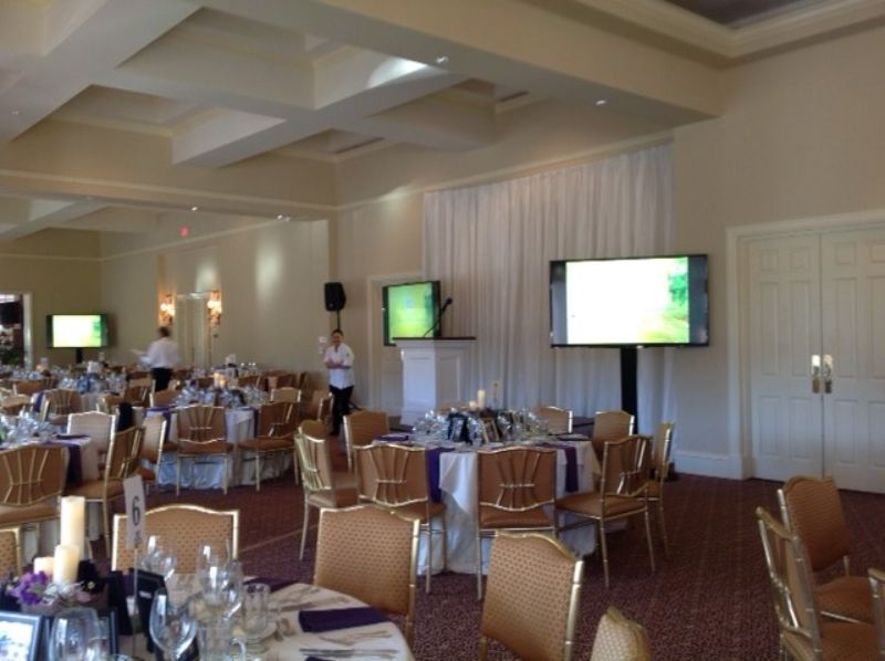 Large room with many tables set up for guests, large TVs set up around the room