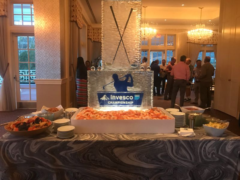 Ice centerpiece with golf clubs for corporate golf event, guests mingling