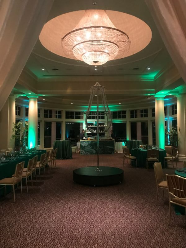 Indoor venue with event lighting, centerpiece, and tables set for guests