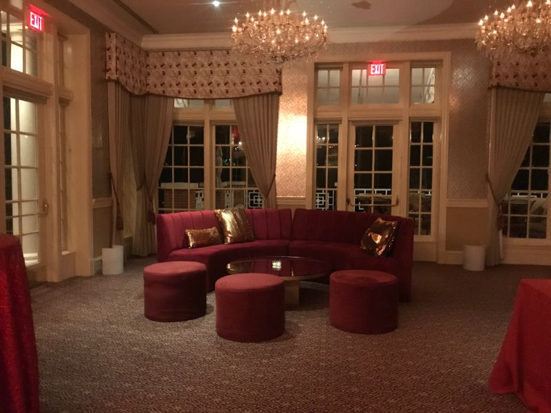 Sitting area at corporate event, burgundy seating with gold pillows