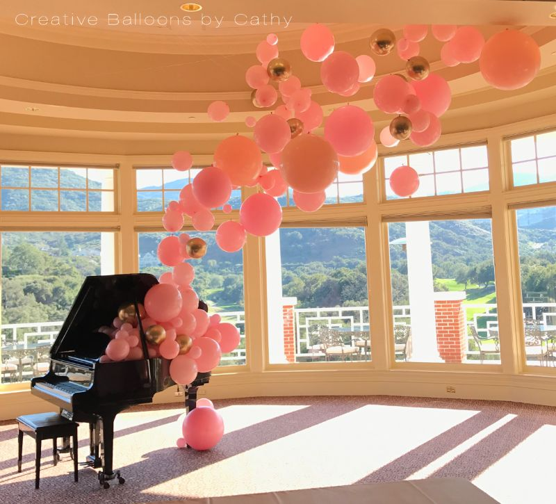 Grand piano with pink balloon display that looks like bubbles