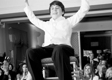 bar mitzvah kid in chair arms over head