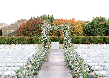 weddings arch with flowers and white chairs